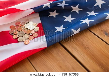 state budget, finance, money, crisis and nationalism concept - close up of american flag and cent coins on wooden boards