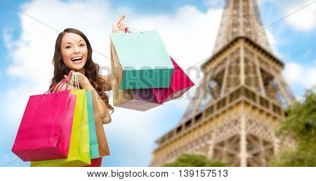 people, holidays, tourism, travel and sale concept - young happy woman with shopping bags over over paris eiffel tower background