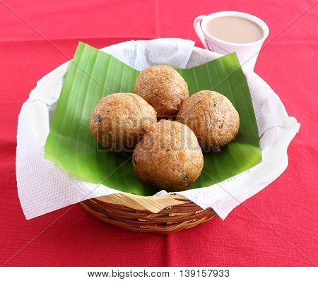 Indian snack, Mangalore bajji, made from deep-frying batter of refined wheat flour and yogurt, native to Mangalore city, Karnataka state, India, in a basket, and tea.