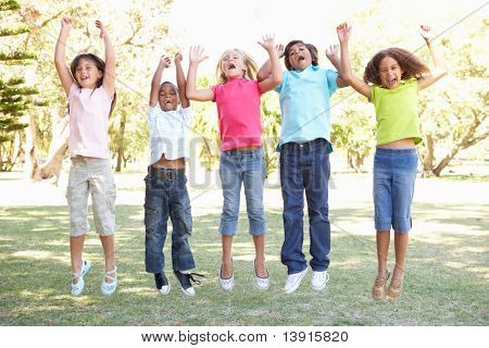 Group Of Children Jumping In Air In Park