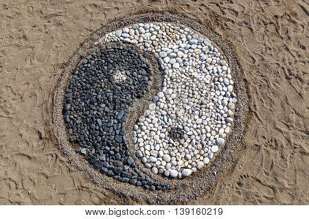 The conception of yin and yang is laid with stones on the sandYin and yang of stones
