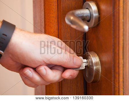 Looking the door with a key. Protect your house by locking the door. Use the key to secure your home