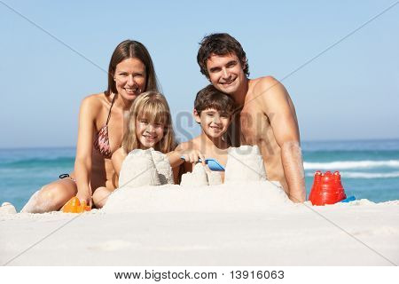 Family Building Sandcastles On Beach Holiday