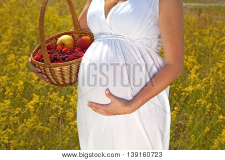 A pregnant girl holding a basket with fruitshealthy pregnancy