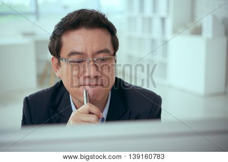 Pensive Asian businessman looking at computer screen