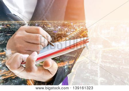 Double exposure of businesswoman  writing the word on a notebook on night cityscape background.