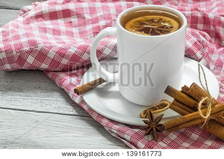 Cup Of Tea On A Red Tablecloth, Beautiful White Wooden Background, Cinnamon Sticks, Lemon And Berrie