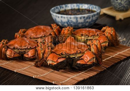 Steamed crabs on bamboo tray with sauces in restaurant