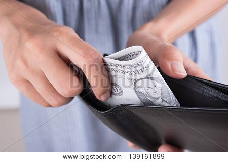 hands show money dollar bills in black wallet. business finance concept