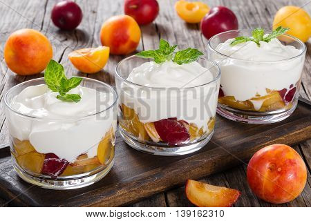 fresh greek yogurt with yellow and red cherry plums in glass cups decorated with mint leaves view from above close-up