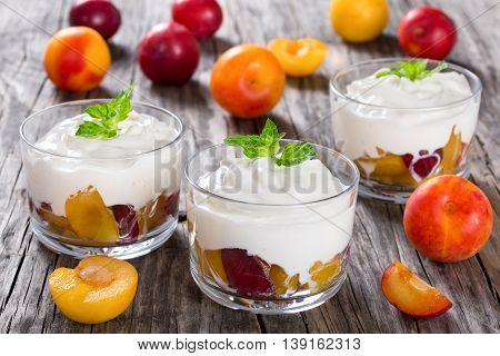 fresh greek yogurt with yellow and red cherry plums in glass cups decorated with mint leaves view from above close-up selective focus