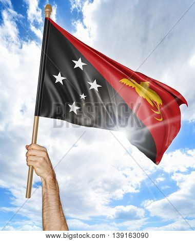 Person's hand holding the Papua New Guinean national flag and waving it in the sky, 3D rendering