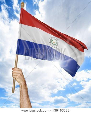 Person's hand holding the Paraguayan national flag and waving it in the sky, 3D rendering
