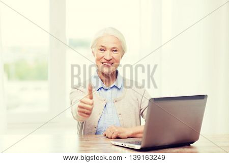 technology, age and people concept - happy senior woman with laptop computer at home showing thumbs up gesture