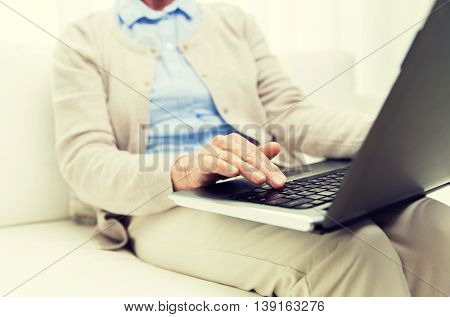 technology, age and people concept - close up of senior woman with laptop computer at home