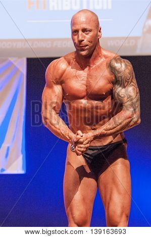 MAASTRICHT THE NETHERLANDS - OCTOBER 25 2015: Male bodybuilders flex their muscles and show their best physique on stage at the World Grandprix Bodybuilding and Fitness of the WBBF-WFF on October 25 2015 at the MECC Theatre in Maastricht the Netherlands.