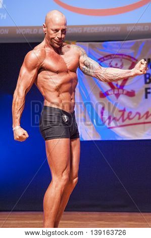 MAASTRICHT THE NETHERLANDS - OCTOBER 25 2015: Male bodybuilder Erik Stobbe shows his best side pose at the World Grandprix Bodybuilding and Fitness of the WBBF-WFF on October 25 2015 at the MECC Theatre in Maastricht the Netherlands.
