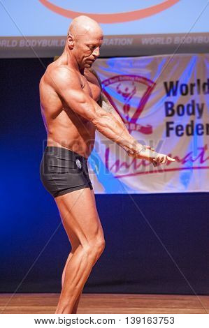 MAASTRICHT THE NETHERLANDS - OCTOBER 25 2015: Male bodybuilder Erik Stobbe shows his best front pose at the World Grandprix Bodybuilding and Fitness of the WBBF-WFF on October 25 2015 at the MECC Theatre in Maastricht the Netherlands.