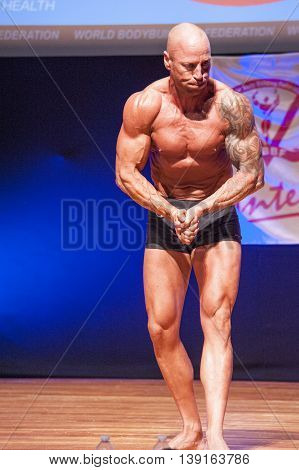 MAASTRICHT THE NETHERLANDS - OCTOBER 25 2015: Male bodybuilder Erik Stobbe shows his best most muscular pose at the World Grandprix Bodybuilding and Fitness of the WBBF-WFF on October 25 2015 at the MECC Theatre in Maastricht the Netherlands.