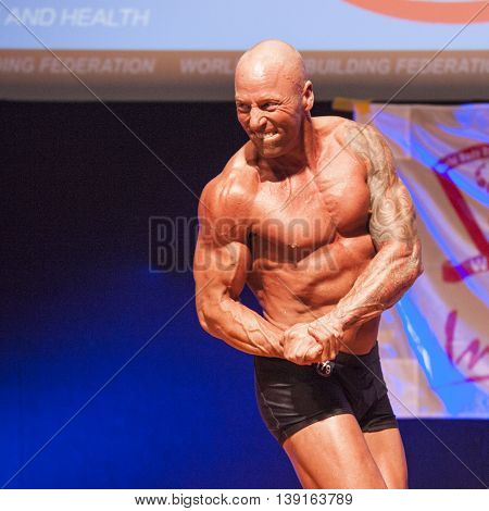 MAASTRICHT THE NETHERLANDS - OCTOBER 25 2015: Male bodybuilder Erik Stobbe shows his best chest pose at the World Grandprix Bodybuilding and Fitness of the WBBF-WFF on October 25 2015 at the MECC Theatre in Maastricht the Netherlands.
