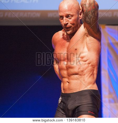 MAASTRICHT THE NETHERLANDS - OCTOBER 25 2015: Male bodybuilder Erik Stobbe shows his best abdominal pose at the World Grandprix Bodybuilding and Fitness of the WBBF-WFF on October 25 2015 at the MECC Theatre in Maastricht the Netherlands.