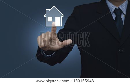 Businessman pressing house icon on blue background Real estate concept
