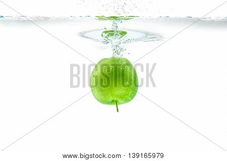 Water splash. Green apple under water. Air bubble and transparent water