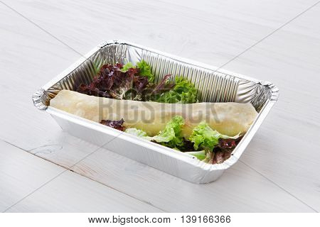 Healthy food delivery and diet concept. Take away of fitness meal. Weight loss nutrition in foil boxes. Flatbread roll with vegetables and lettuce at white wood