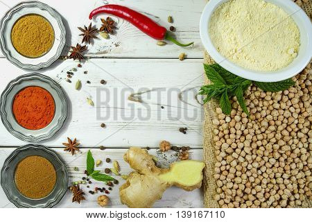 Colorful Indian food ingredients - chickpea ginger gram flour and spices on white wooden table top