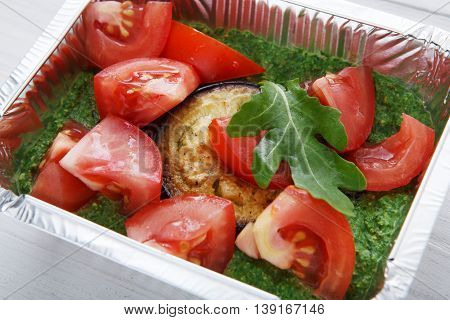 Healthy food delivery and diet concept. Take away of fitness meal. Weight loss nutrition in foil boxes. Roasted eggplant with guacamole and fresh tomatoes, closeup at white wood