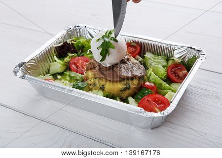 Restaurant food delivery in foil box. Knife tip starts to cut poached egg on veil steak medium rare with fresh vegetable salad and couscous cushion. Dish take away closeup, healthy meal.
