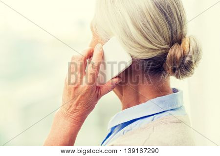technology, communication, age and people concept - close up of senior woman with smartphone calling at home