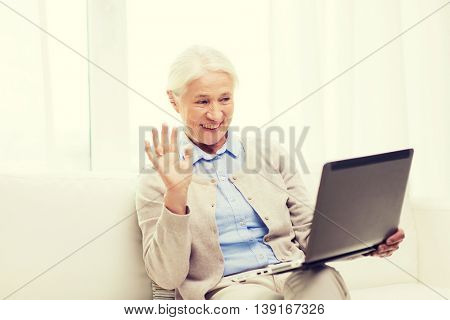 technology, age, gesture, communication and people concept - happy senior woman with laptop computer having video chat at home and waving hand