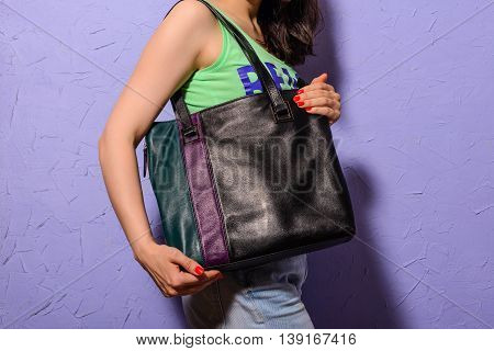 Young stylish woman with black trendy big bag in hand indoors
