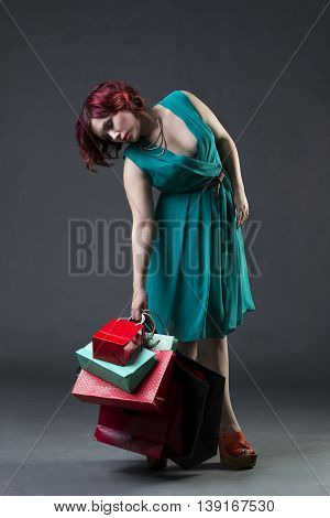 Shopaholic concept young beautiful red-haired caucasian woman in aquamarine dress posing in studio on gray background professional makeup and hairstyle full-length portrait