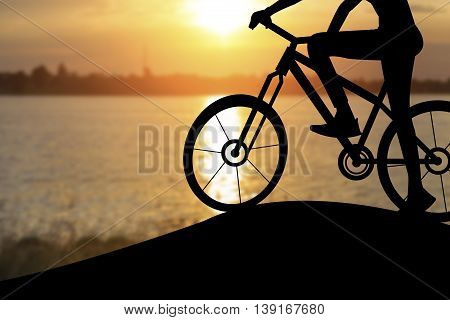 Silhouette Of A Woman On Muontain Bike, Sunset.