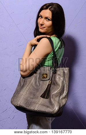 Attractive young brunette girl with a big bag of snake skin posing iris background