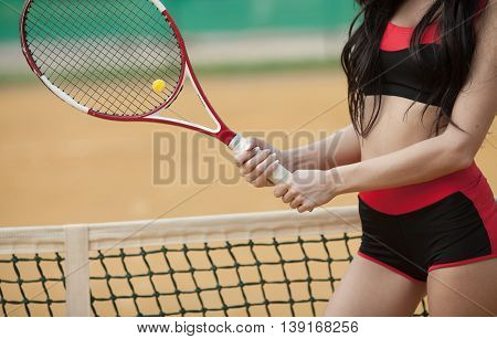 Closeup female hand with tennis racket on court