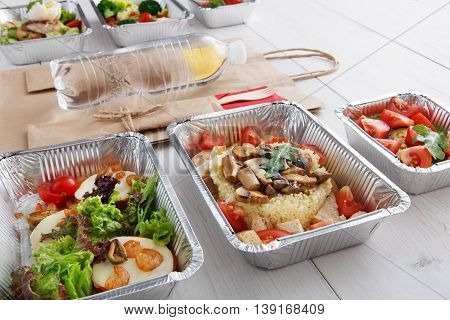 Healthy food and diet concept. Take away of fitness meal. Weight loss nutrition in foil boxes and brown paper package bag with water bottle. Couscous and mozarella with shrimps at white wood
