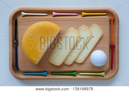 Block of tasty cheese on cutting board with a knife and golf tees isolated on white wooden desk