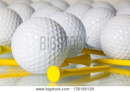 Different golf balls and yellow tees on a glass table