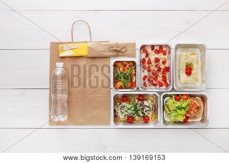 Healthy food delivery, daily meals and snacks. Diet nutrition, vegetables, berry oatmeal, meat and water bottle in foil boxes and brown paper package. Top view, flat lay at white wood with copy space