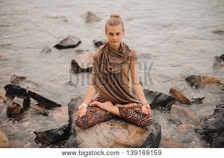 Young woman in lotus pose meditating on rock seaside