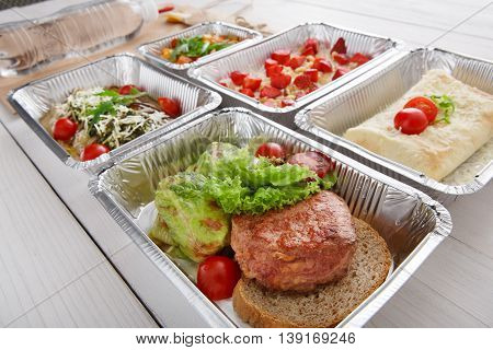 Healthy restaurant food delivery in foil box. Green stewed cabbage roll with veal steak on brown bread and other dishes. Beef and vegetable with cherry tomato. Meals take away closeup.