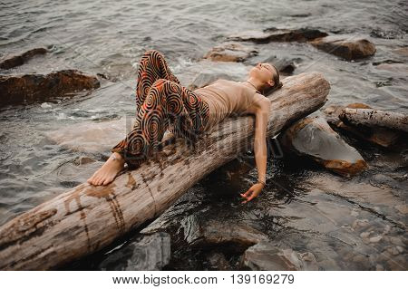 Dreaming young woman is lying on the log at the sea