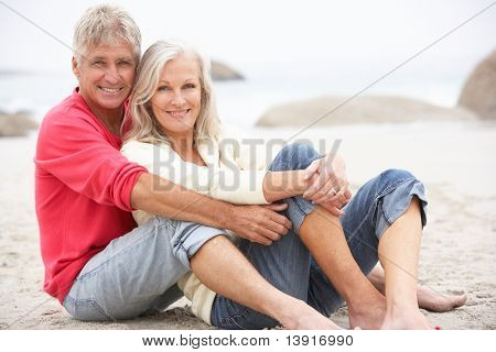 Senior Couple On Holiday Sitting On Winter Beach