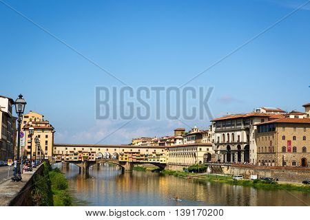 FLORENCE, ITALY - AUGUST 25, 2015, View of medieval stone bridge Ponte Vecchio and the Arno River from the Ponte Santa Trinita in Florence, Tuscany, Italy. Florence is a popular tourist destination.