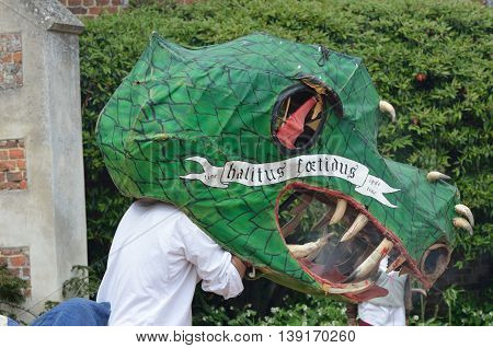 Kentwell Hall England United Kingdom - May 05 2014: Man with large Dragon head and George and the Dragon traditional play