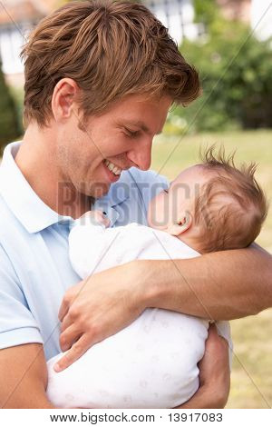 Close Up Of Father Cuddling Newborn Baby Boy Outdoors At Home