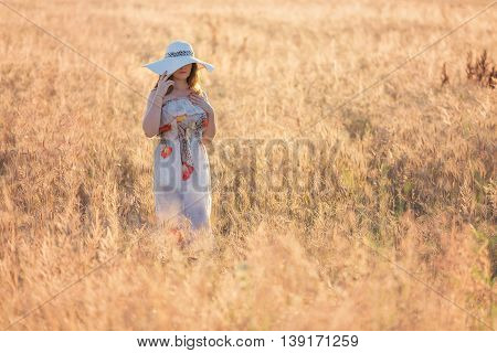 Summer portrait of a young woman, wearing a white hat, in the wheat field, at sunset